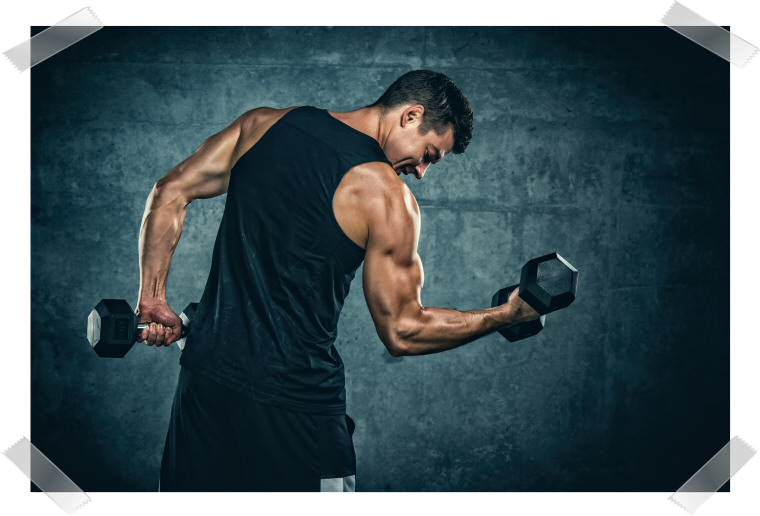 A photograph of a muscular man lifting dumbbels one at a time.