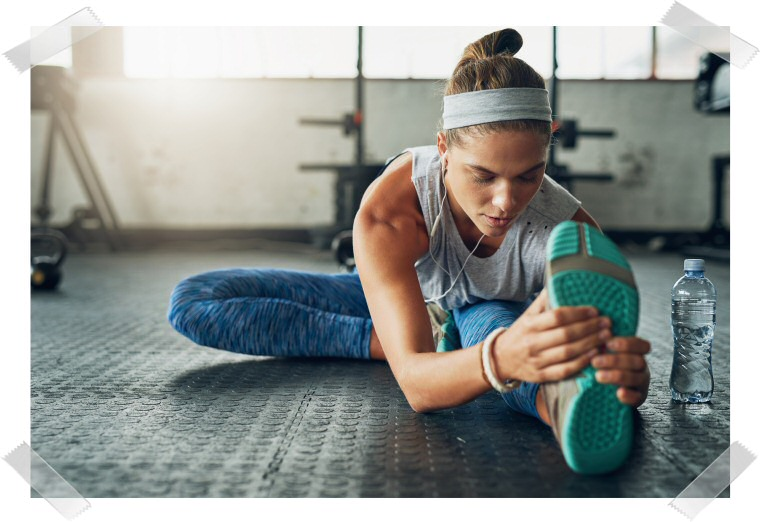 Picture of a young woman stretching her body towards the feet. Next to her is a water bottle.